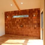 奥様の希望のリビングの壁はレッドシダーを使用。 白い珪藻土の中に赤い木の板が映えて、おしゃれな仕上がりになっています。